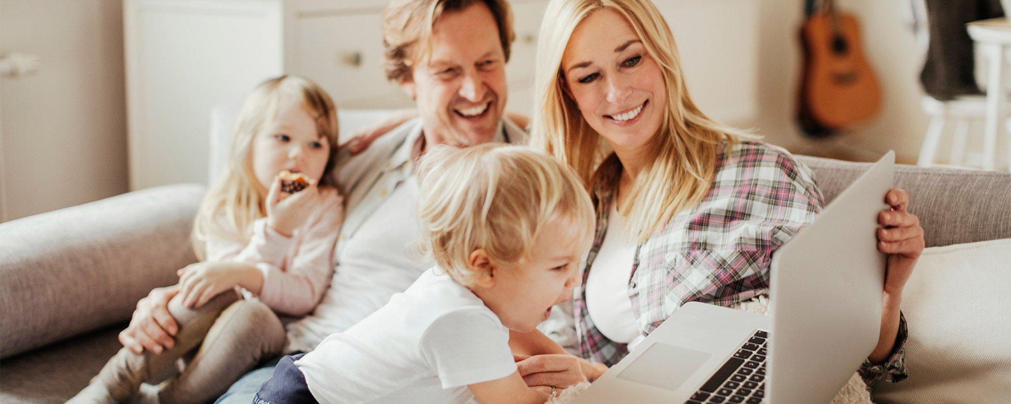 Kuvassa mies ja nainen sekä kaksi lasta tutkivat kannettavan tietokoneen näyttöä.