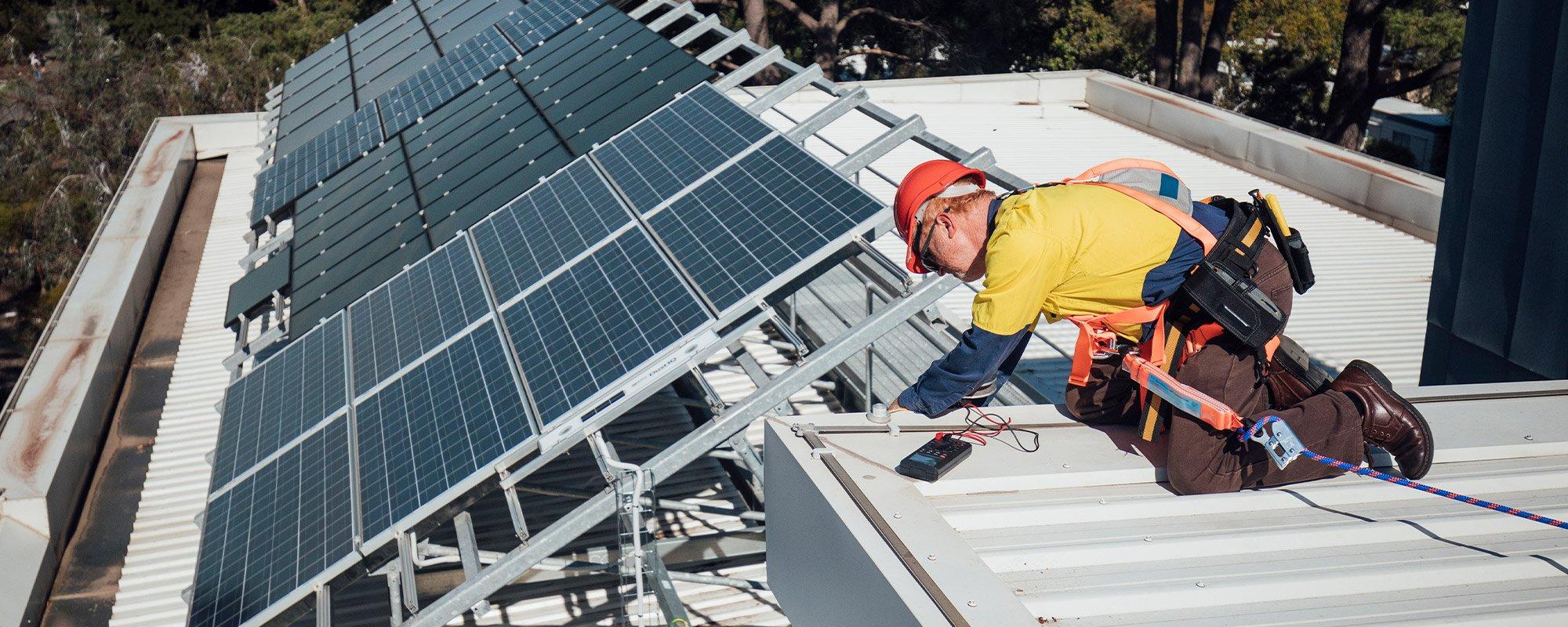 Mies katolla asentamassa aurinkopaneeleja