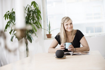 Opiskelijatyttö kahvikuppi kädessä, kuvituskuva.