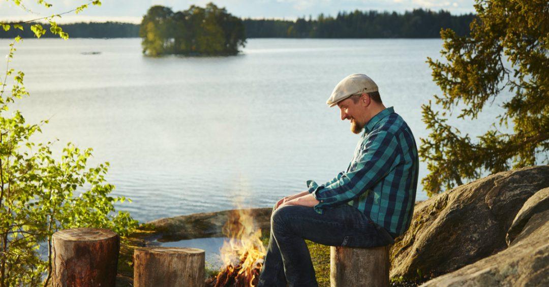 Mies nuotiolla järven rannassa, kuvituskuva