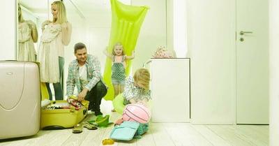 Perhe pakkaamassa lomalle, kuvituskuva.
