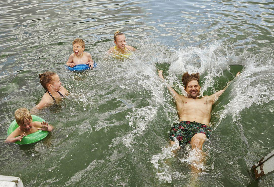 Isä ja lapset uimassa, kuvituskuva.